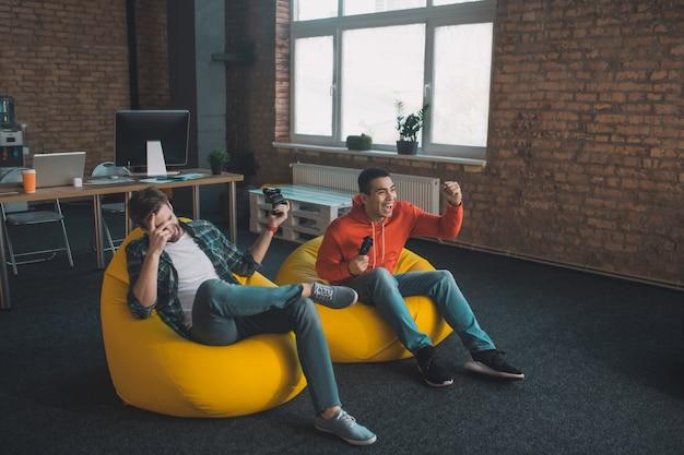 Szczęśliwi młodzi mężczyźni spędzający weekend podczas grania w gry w domu
