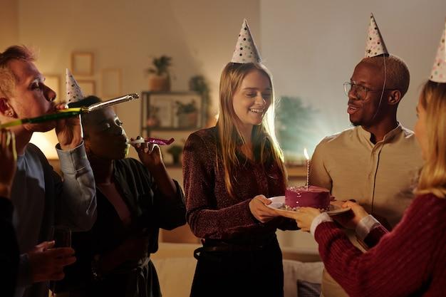 Szczęśliwi młodzi międzykulturowi przyjaciele gratulują wspaniałej blond dziewczynie z okazji jej urodzin, podczas gdy ładna kobieta podaje talerz z pysznym ciastem
