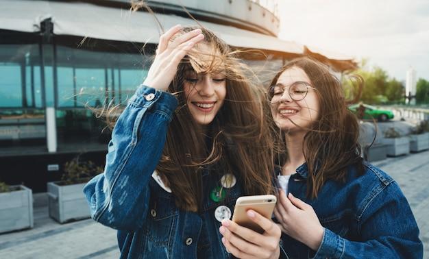 Szczęśliwi młodzi najlepsi przyjaciele używają mediów społecznościowych na swoich smartfonach