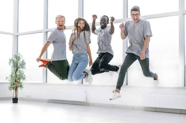 Szczęśliwi młodzi pracownicy bawią się w nowym biurze