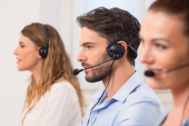 Szczęśliwi młodzi pracownicy pracujący w call center. portret młodego atrakcyjnego operatora telefonicznego pracującego w centrum obsługi telefonicznej. przedstawiciel obsługi klienta w biurze w zestawie słuchawkowym.