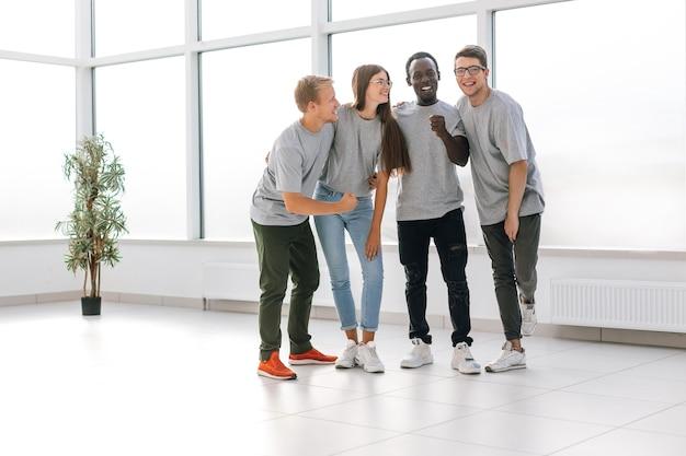 Szczęśliwi młodzi pracownicy stojący w nowym biurze