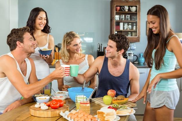 Szczęśliwi młodzi przyjaciele ma śniadanie przy stołem