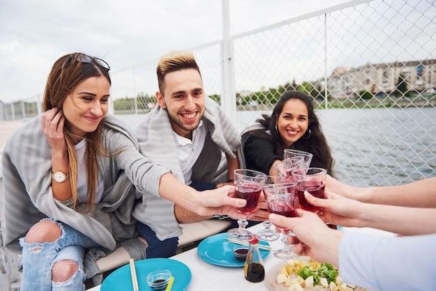 Szczęśliwi młodzi przyjaciele siedzieli przy stole i urządzali piknik na świeżym powietrzu.