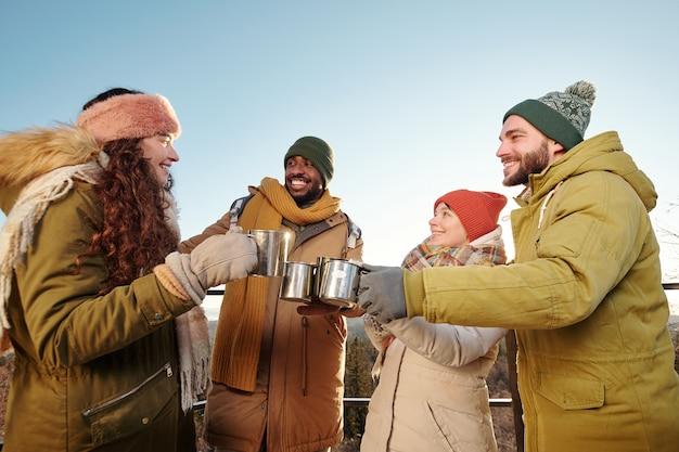 Szczęśliwi młodzi przyjaciele w zimowych strojach rozweselających gorącą herbatą i rozmawiających na tle błękitnego nieba nad górami i lasem w zimowy weekend