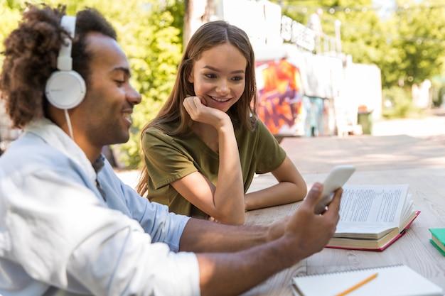 Szczęśliwi młodzi przyjaciele wieloetniczni studenci rozmawiają ze sobą