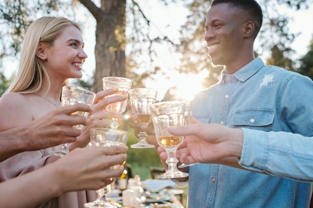 Szczęśliwi młodzi randki międzykulturowe spoglądające na siebie z zębatymi uśmiechami, brzęczące kieliszkami wina w gronie przyjaciół na świeżym powietrzu