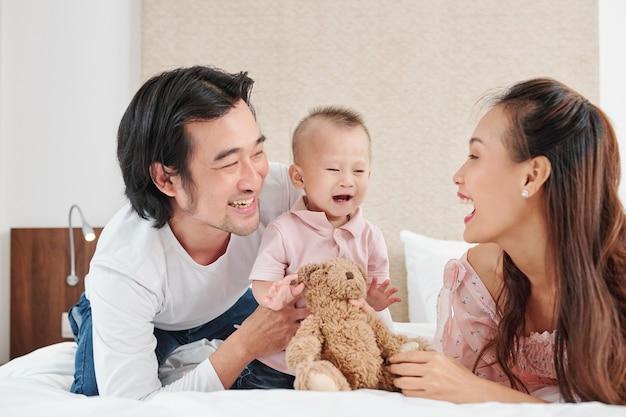 Szczęśliwi młodzi rodzice dają zabawki swojemu chłopcu i próbują go rozśmieszyć