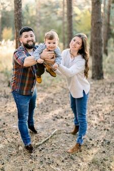 Szczęśliwi młodzi rodzice i mały synek, spacerujący razem na świeżym powietrzu w jesiennym lesie lub parku, trzymając dziecko na rękach i pozując do aparatu z uśmiechem