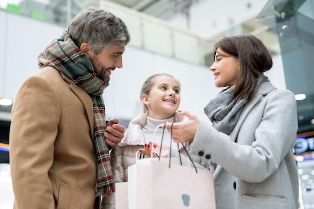Szczęśliwi młodzi rodzice patrząc na swoją córkę, podczas gdy matka pokazuje nowy zakup w papierowej torbie po zakupach