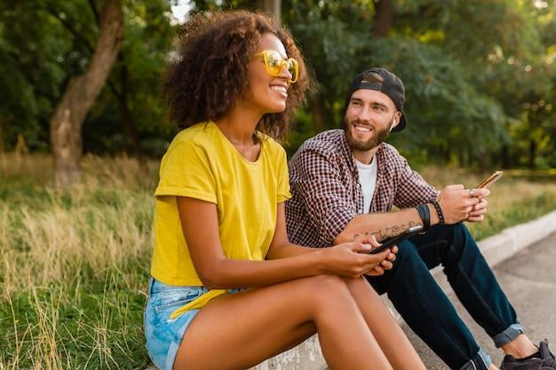 Szczęśliwi młodzi uśmiechnięci przyjaciele siedzi w parku za pomocą smartfonów, mężczyzna i kobieta, wspólna zabawa