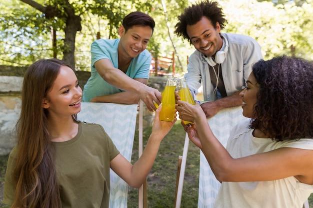 Szczęśliwi młodzi wieloetniczni przyjaciół ucznie outdoors pije sok