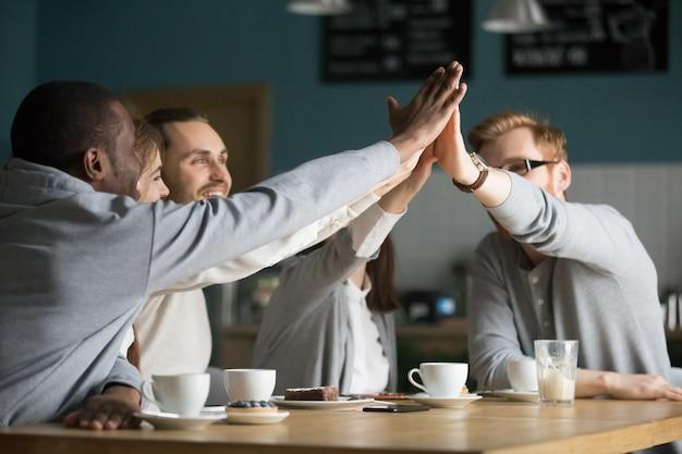 Szczęśliwi multiracial przyjaciele kawiarni daje wysokości przy spotkaniem w kawiarni