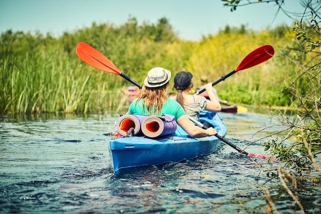Szczęśliwi najlepsi przyjaciele bawią się na kajakach. spływy kajakowe po rzece.