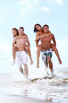 Szczęśliwi nastolatkowie bawić się przy morzem