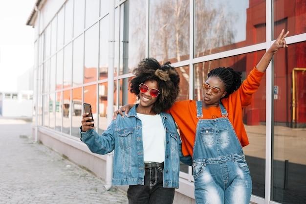Szczęśliwi nastolatkowie bierze selfie wpólnie