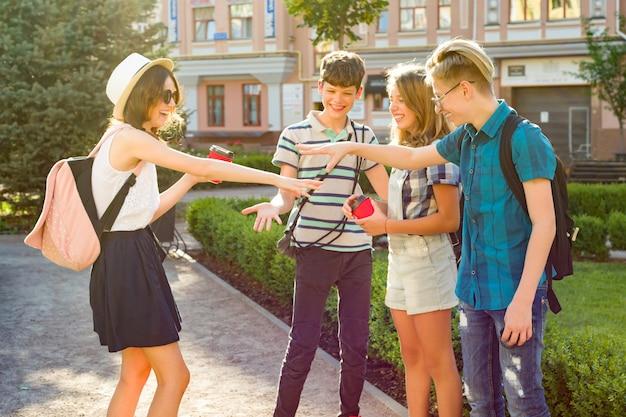 Szczęśliwi nastolatkowie przyjaciele chodzą, rozmawiają ciesząc się dniem w mieście