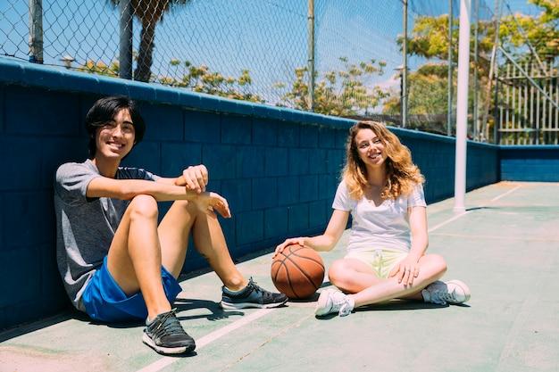 Szczęśliwi nastolatkowie siedzi w boisko do koszykówki