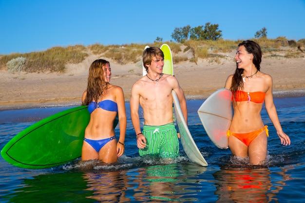 Szczęśliwi nastoletni surfingowowie opowiada na plażowym brzeg