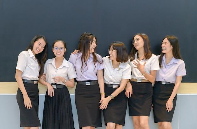 Szczęśliwi nastoletni ucznie stoi wpólnie w sala lekcyjnej