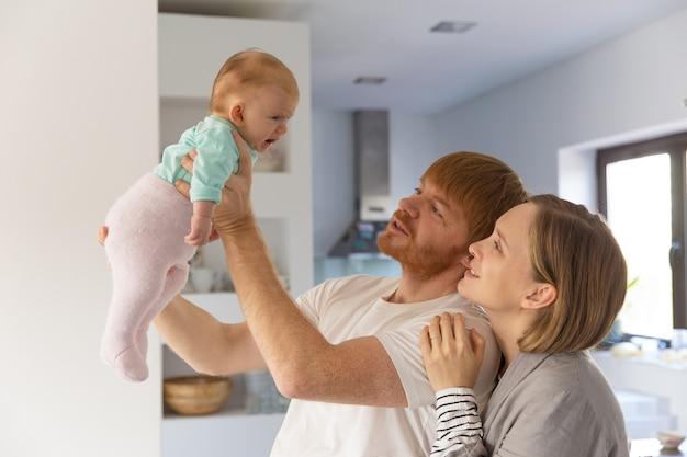 Szczęśliwi nowi rodzice trzyma płaczu dziecka i patrzeje