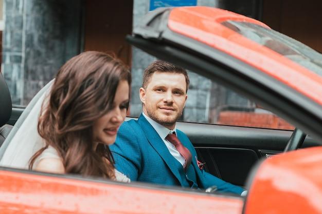 Szczęśliwi nowożeńcy jadą na uroczystość czerwonym samochodem z odkrytym dachem. koncepcja ślubu
