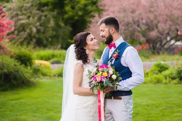 Szczęśliwi nowożeńcy na zielonym trawniku