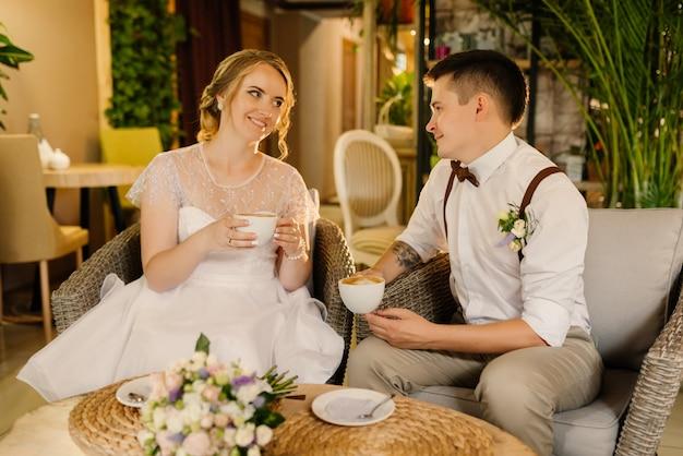 Szczęśliwi nowożeńcy patrzą na siebie i piją kawę, trzymają w rękach kubki z kawą. parada miłości w przytulnym wnętrzu kochająca się para przed ślubem.