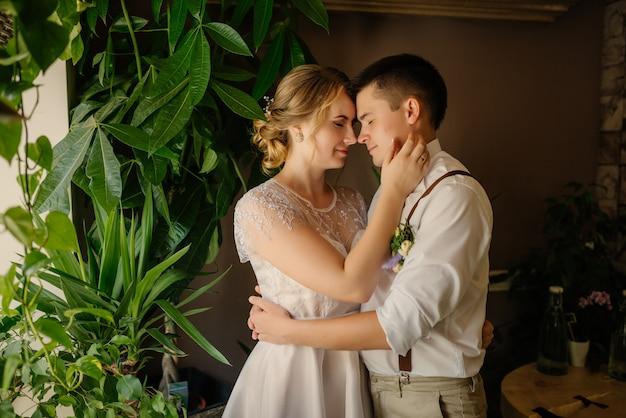 Szczęśliwi nowożeńcy pochylają się, kłaniając przed sobą głowami przed zielonymi plantacjami.
