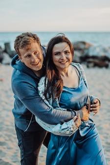 Szczęśliwi nowożeńcy pozowanie na plaży. dziewczyna w niebieskiej sukience z długimi, obcisłymi włosami i facet o niebieskich oczach.