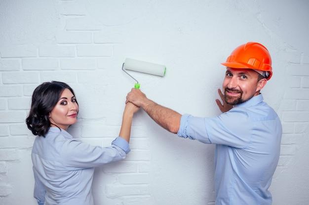 Szczęśliwi nowożeńcy rodzina przystojny mężczyzna w kasku budowlanym kask i urocza kobieta razem maluje biały ceglany mur w domu. koncepcja kupna, remontu i budowy w mieszkaniu domowym