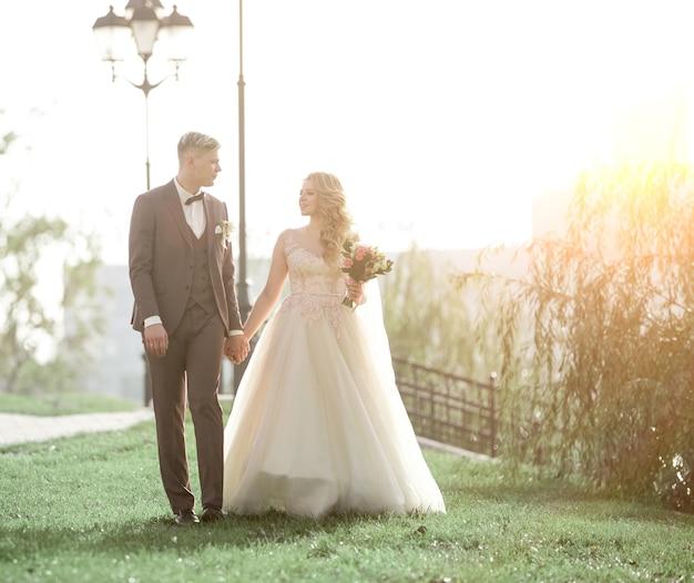 Szczęśliwi nowożeńcy spaceru na trawie w parku miejskim. zdjęcie z miejscem na kopię