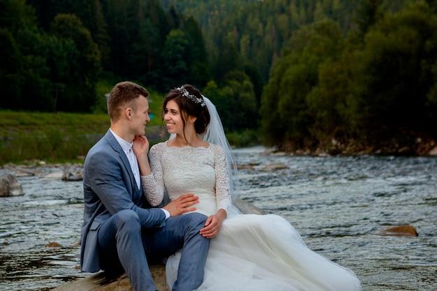 Szczęśliwi nowożeńcy stoi i ono uśmiecha się na rzece. nowożeńcy, zdjęcie na walentynki