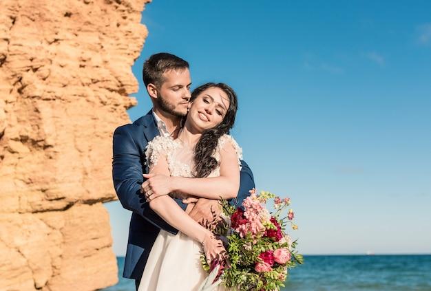 Szczęśliwi nowożeńcy stoją trzymając się za ręce na tle błękitnego morza. weselny spacer po piaszczystej plaży. w tle błękitne niebo