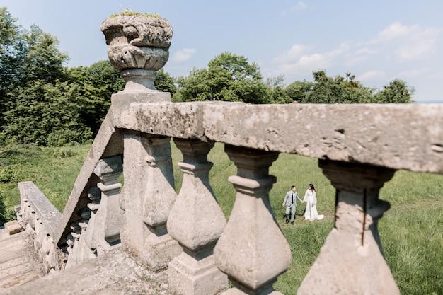Szczęśliwi nowożeńcy stoją trzymając się za ręce na tle starego zamku