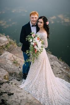 Szczęśliwi nowożeńcy stojąc i uśmiechając się na brzegu rzeki