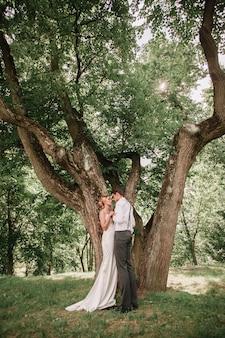 Szczęśliwi nowożeńcy stojący w pobliżu dużego rozłożystego drzewa. romantyczny moment