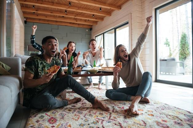 Szczęśliwi pięciu przyjaciół siedzi w domu i je pizzę