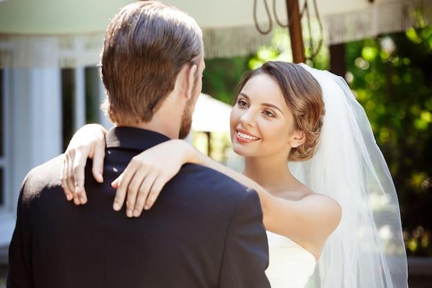Szczęśliwi piękni nowożeńcy uśmiechający się, obejmujący, patrzący na siebie.