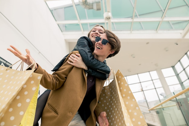 Szczęśliwi piękni potomstwa dobierają się mień torba na zakupy podczas gdy stojący w centrum handlowym.