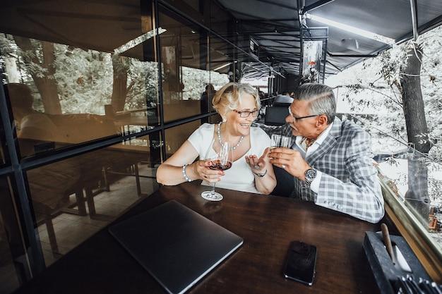 Szczęśliwi piękni starsi ludzie piją wino przy stole na letnim tarasie w nowoczesnej kawiarni