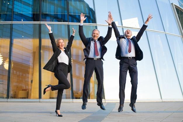 Szczęśliwi podekscytowani ludzie biznesu razem świętują sukces, skaczą i krzyczą. pełna długość, widok z przodu. udana koncepcja zespołu i pracy zespołowej