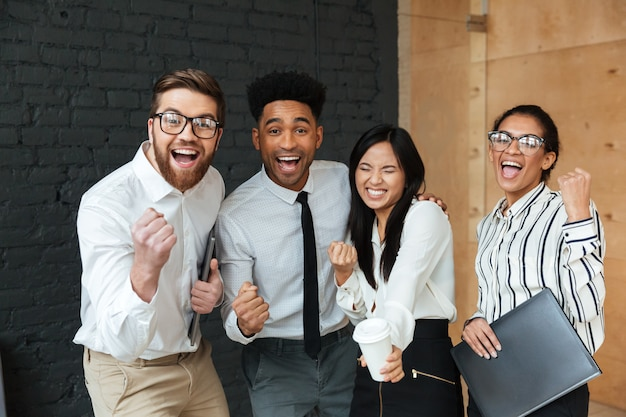 Szczęśliwi podekscytowani młodzi biznesowi koledzy robią zwycięzcy gestowi.