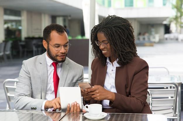 Szczęśliwi podekscytowani partnerzy biznesowi korzystający z gadżetów
