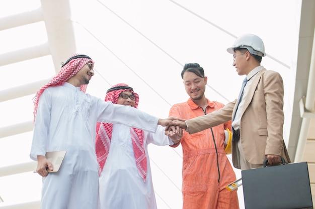 Szczęśliwi pomyślni arabscy mężczyzna i azjatykci biznesowi mężczyzna na miasta tle