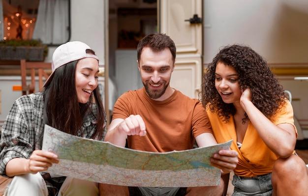 Szczęśliwi poszukiwacze przygód przyjaciele patrząc na mapę