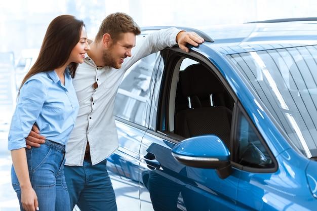 Szczęśliwi potomstwa dobierają się patrzeć inside nowy samochód przy samochodowym salonem