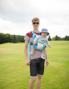 Szczęśliwi potomstwa ojcują z dzieckiem w temblaku z przodu ma spacer outside w parku lub zielonej łące