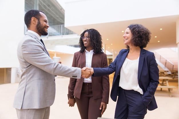 Szczęśliwi pozytywni partnerzy biznesowi kończący spotkanie