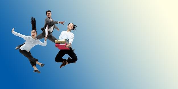 Szczęśliwi pracownicy biurowi skaczą i tańczą w zwykłych ubraniach lub garniturach na gradientowym neonu